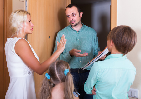 confiscation: Family and irritated inspector having conversation at entrance