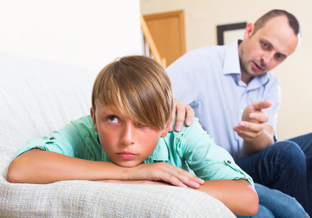 stubborn: Man trying to reconcile with stubborn teenager  after quarrel Stock Photo