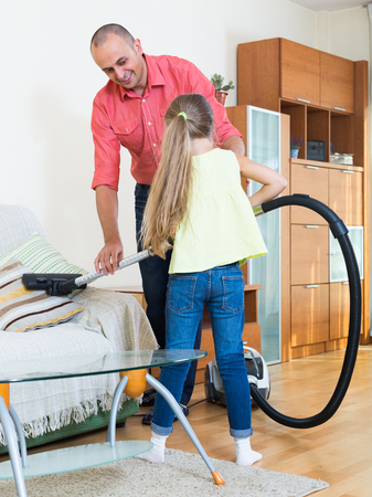 teaching adult: Smiling adult man teaching little girl vacuuming during clean-up