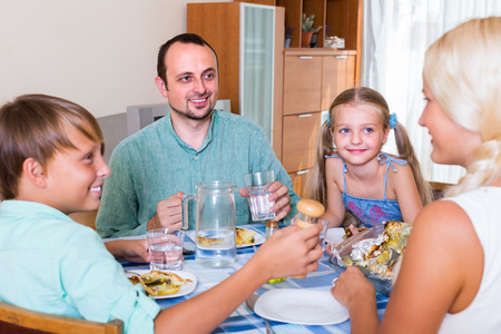 familia cenando: Padres felices y niños que tienen cena familiar en interiores