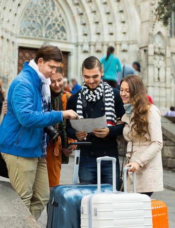 group direction: Group of friends with luggage checking direction in map outdoor Stock Photo