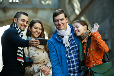 mutual: Group of smiling friends shooting mutual portrait on cell phone outdoors