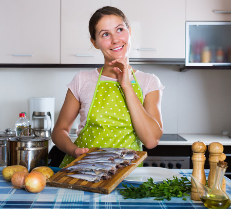 loathsome: Happy young woman cooking stew with sardines and smiling Stock Photo
