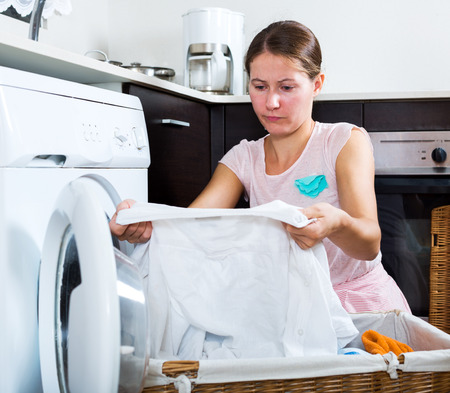 white shirt: Unhappy young housewife with dirty white shirt near washing machine Stock Photo