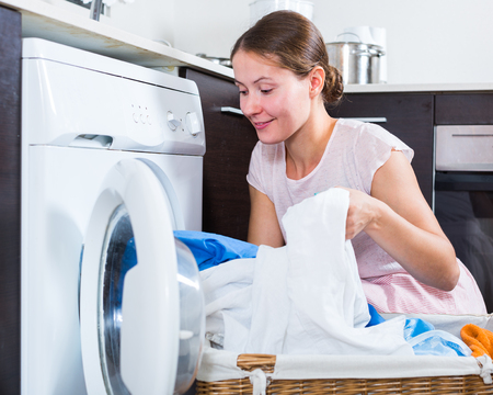 lavanderia: Positive young woman 25-30 years old doing laundry at home Foto de archivo