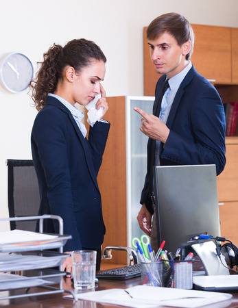 lecturing: Stressed manager scolding employee for work mistakes indoors