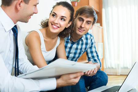 Positive sales consultant with laptop explaining young couple conditions of purchase