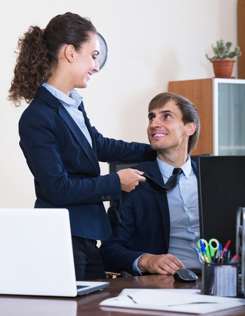 seducer: happy top manager flirting with adult subordinate official at workplace