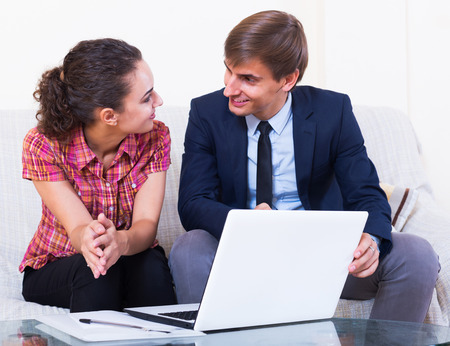 conduction: Insurance agent and positive customer discussing agreement terms and smiling