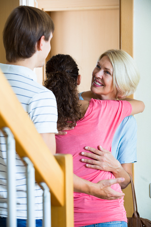come home: Young family couple welcoming senior mother at door and smiling