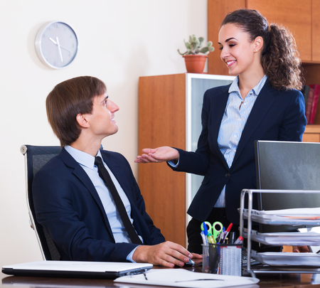 successfully: Smiling office colleagues successfully working together indoors Stock Photo