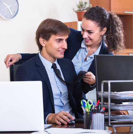molestation: Sexual harassment in office: female director flirting with employee and smiling Stock Photo