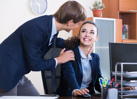 the tempter: Top manager flirting with smiling european adult subordinate official at workplace Stock Photo