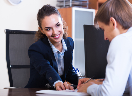 job occupation: Young professional teaching new employee in practice at company