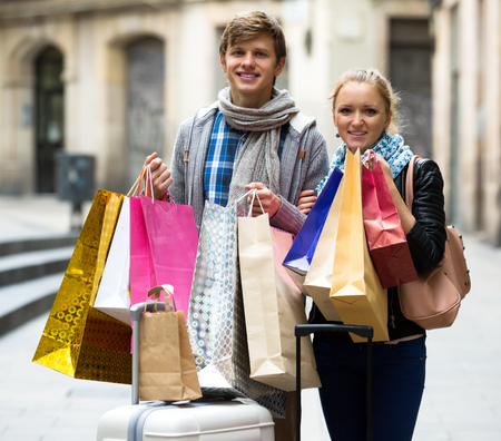 the spouse: Smiling spouse walking through European town and carrying shopping bags