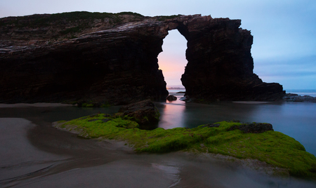 turistic: Natural arch at  As Catedrais beach in sunrise- it is the turistic name of Praia de Augas Santas (Beach of the Holy Waters). Galicia,   Spain