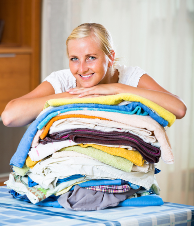 sorting out: Happy smiling blonde girl sorting out laundry at home