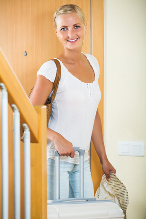 interphone: Happy blonde girl standing with luggage near entrance indoors Stock Photo