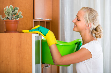 dusting: Happy young blonde woman in rubber gloves dusting furniture at home