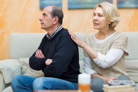 flatter: Worried mature woman assuaging man of anger indoors. Focus on woman