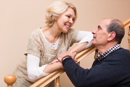 spouses: Portrait of happy senior spouses holding hands and looking at each other near staircase