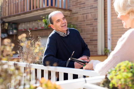 retired couple: Portrait of retired couple on a terrace: old husband is holding a cup of hot beverage and talking to his wife who is holding gardening tools Stock Photo