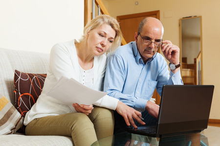 parsimony: serious mature couple with financial documents and laptop in home interior