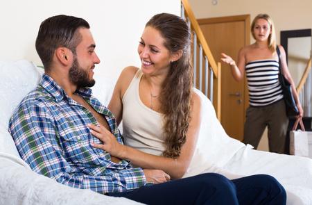 marido y mujer: Mujer joven rubia viendo cómo su marido la engaña con otra chica