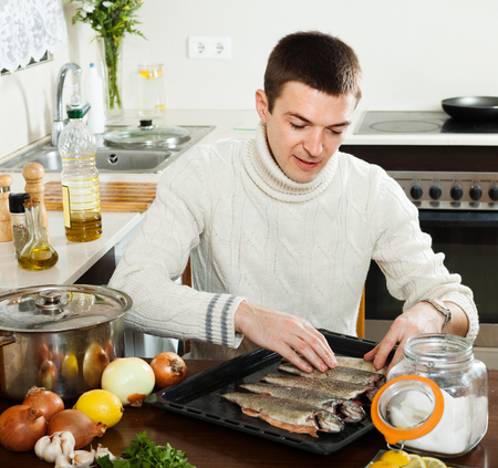 roasting pan: guy cooking raw fish  in roasting pan at home kitchen Stock Photo