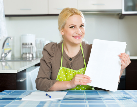 utility payments: Young smiling woman with paper at home kitchen