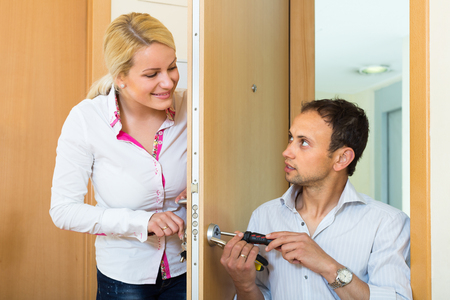 25s: Young man with tools repairing door lock for blonde smiling housewife