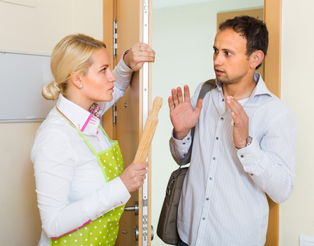 conflict: Serious conflict between wife and husband at the door Stock Photo