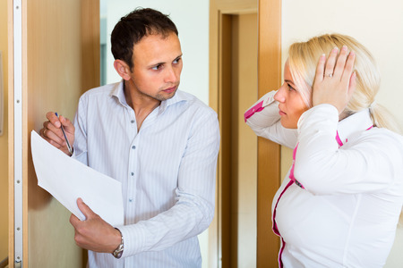 Businessman trying to collect arrearages from housewife. Selective focus on woman