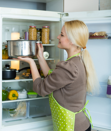 fridge: Blonde russian girl looking for something in fridge at home kitchen