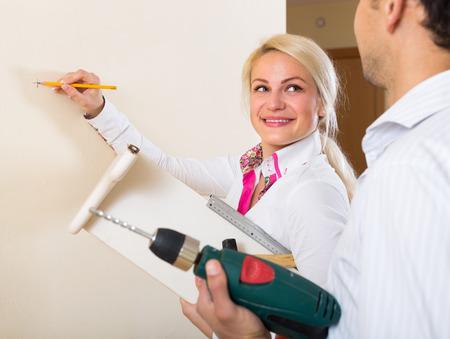 repairs: Smiling young family makes repairs in apartment