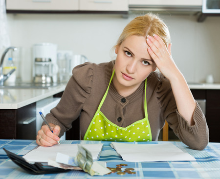 financial problems: Sad  young american woman thinking about the financial problems  at home
