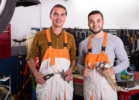 car service station: Portrait of two happy mechanics posing with tools at a car service station Stock Photo