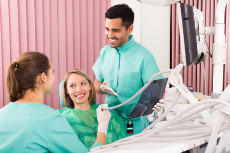 a dentist: Dentist and american patient looking x-ray results in clinic Stock Photo