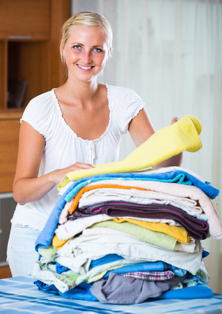sorting out: Cheerful young  blonde woman sorting out laundry at home Stock Photo