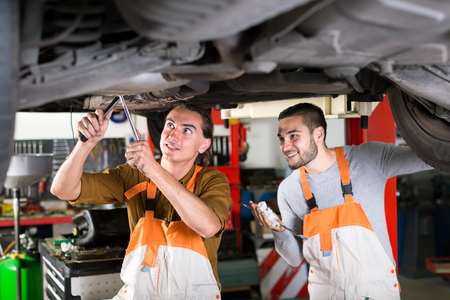 shop skill: Happy mechanics repairing exhaust system on a lifted up sedan car in a car repair shop Stock Photo
