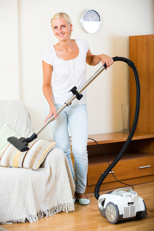 regular people: Smiling young blonde woman in jeans vacuuming furniture at home