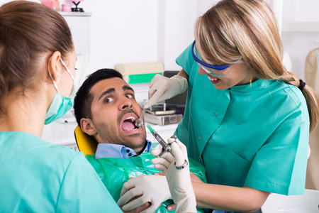 Dentist with assistant and scared patient during check up at dental clinic