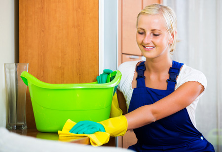 cleanup: Professional female cleaner doing regular clean-up in livingroom Stock Photo