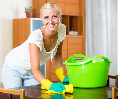 regular people: Cheerful girl in rubber gloves dusting furniture in living room and smiling