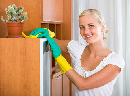 dusting: Happy young woman in rubber gloves dusting furniture at home