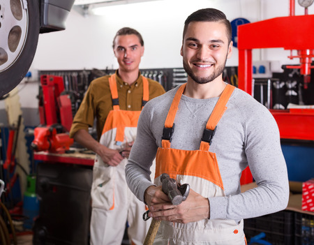 toiling: Two positive workmen toiling in locksmiths workshop and smiling