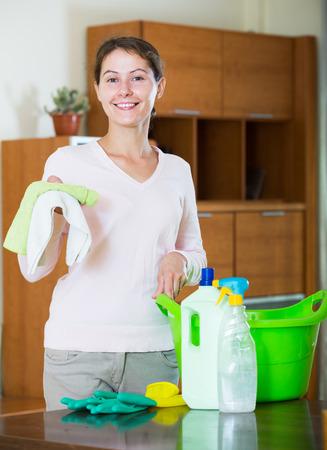 regular: Positive american housewife doing regular clean up in living room