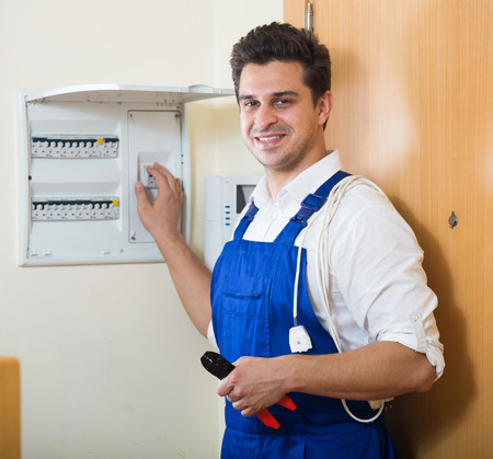 electric meter: Professional handyman near electric meter in domestic interior