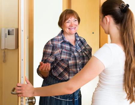 personas saludandose: Dos mujeres sonriendo adultos de pie junto a la puerta Foto de archivo