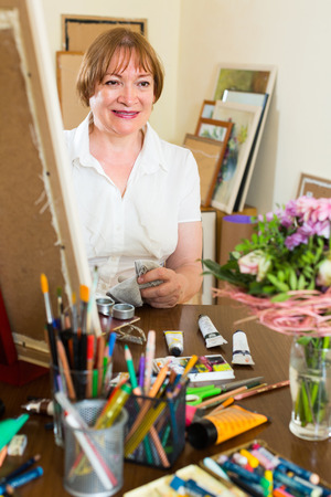 contentedness: Happy smiling mature woman painting for fun with paints at home Stock Photo